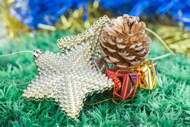 Decoraciones y ornamentos de la Navidad en fondo de la hierba verde imágenes de archivo libres de regalías