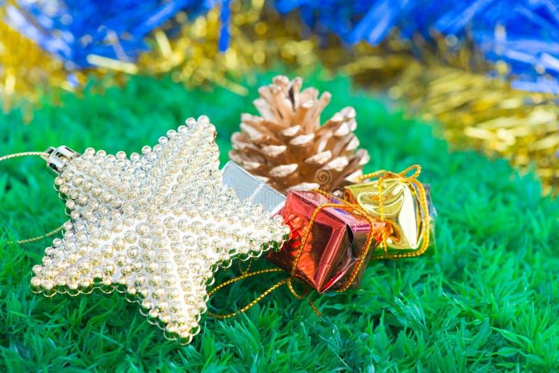 Decoraciones y ornamentos de la Navidad en fondo de la hierba verde foto de archivo