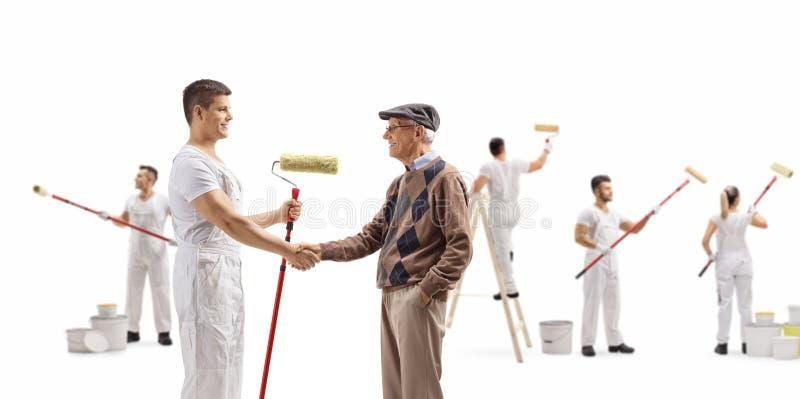 Decorador con un pintor del rodillo que sacude las manos con una pared de pintura del mayor y de la gente foto de archivo libre de regalías