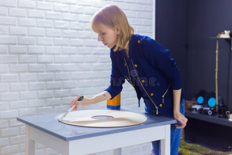 Decorador da mulher profissional, desenhista que pinta a decoração de madeira do círculo imagens de stock royalty free