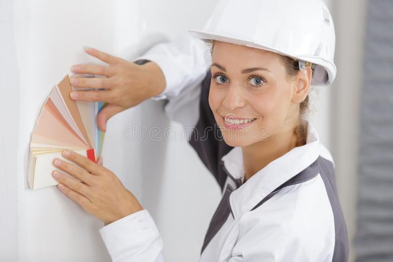 Decorador de sexo femenino que lleva a cabo la carta de la pintura contra la pared fotografía de archivo