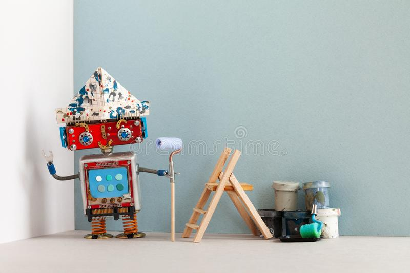 Decorador do pintor do robô do smiley com as cubetas do rolo de pintura e a escada de madeira Conceito interior do apartamento da fotografia de stock