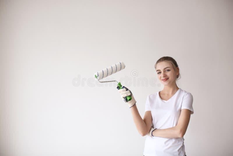 Decorador fêmea com o rolo de pintura no fundo claro imagens de stock