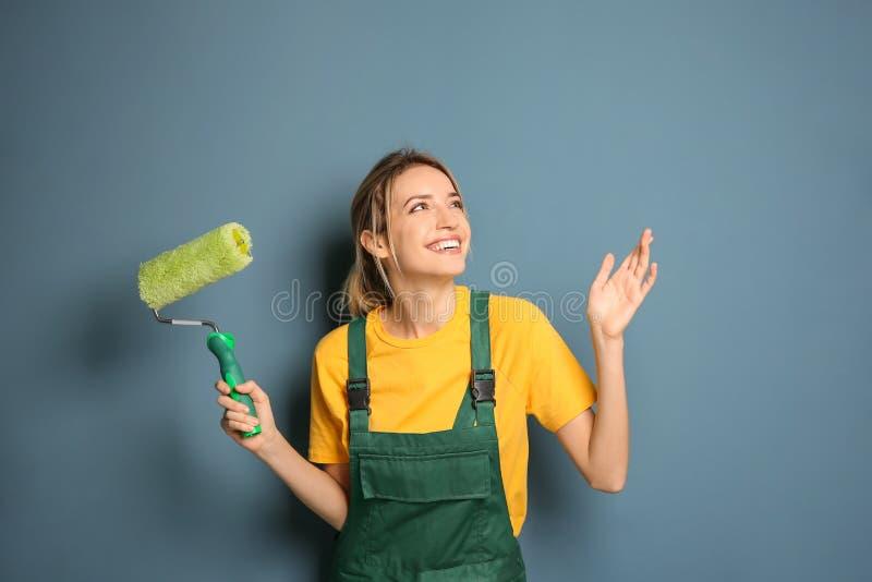 Decorador fêmea novo com rolo de pintura imagens de stock