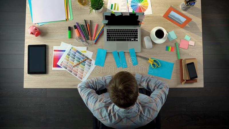 Decorador interior que olha o papel colorido para notas, trabalhos criativos do corte fotos de stock
