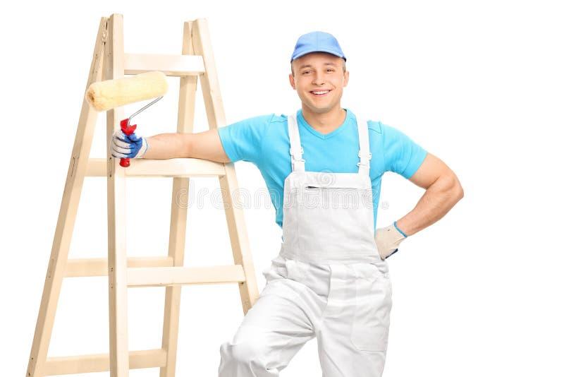 Decorador masculino alegre que guarda um rolo de pintura imagem de stock