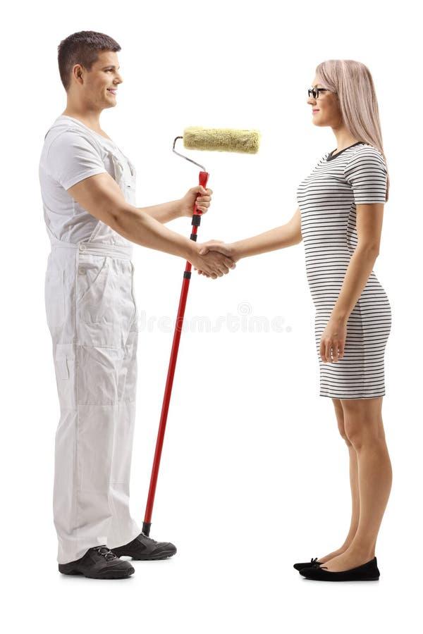 Decorador masculino com um pintor do rolo que agita as mãos com uma jovem mulher fotografia de stock