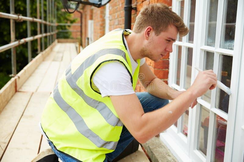 Decorador no andaime que pinta a casa exterior Windows imagens de stock royalty free