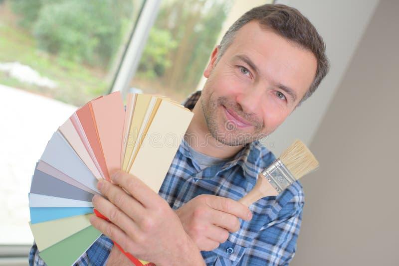 Decorador novo que guarda amostras da cor e escova de pintura foto de stock royalty free
