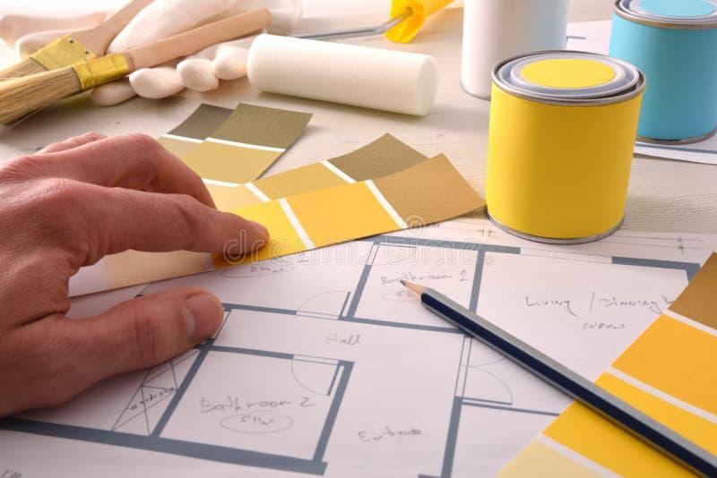 Decorador que escolhe a cor amarela para o projeto interior da pintura da casa fotografia de stock royalty free