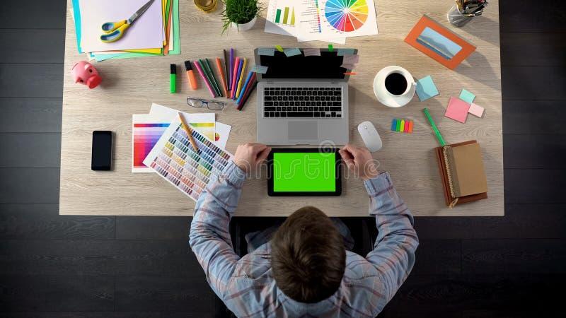Decorador que swiping a tabuleta com tela verde, plano de vista do apartamento do cliente fotos de stock