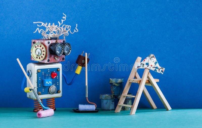Decorador robótico engraçado do pintor pronto para a manutenção interior Escada, rolo de pintura e cubetas de madeira contra o az fotografia de stock royalty free