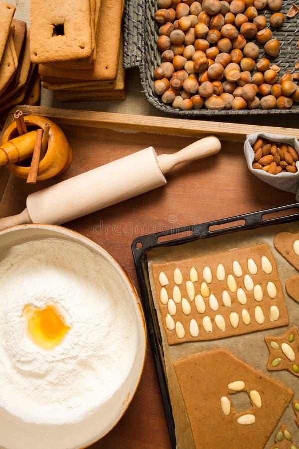 Decorando os biscoitos do pão-de-espécie nuts imediatamente antes do cozimento imagens de stock