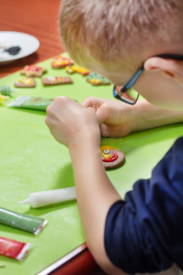Decorando cookies da canela por uma criança As mãos do menino formam uma cara da crosta de gelo colorida espremida fora dos tubos fotografia de stock royalty free