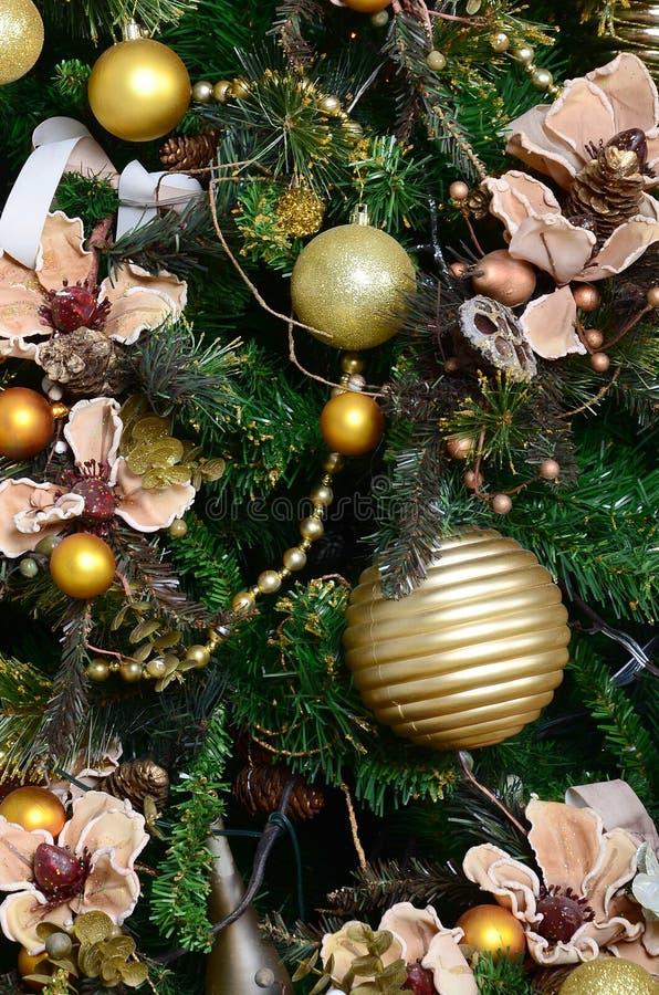 Decorando fine dell'albero di Natale su Lampadina della decorazione, albero di abete verde, giocattoli dorati di natale e luci Us immagine stock