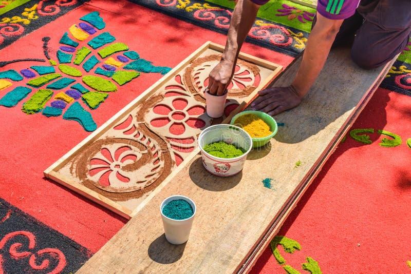 Decorando o tapete santamente tingido de quinta-feira da serragem, Antígua, Guatemala fotos de stock