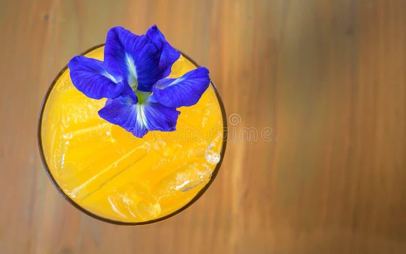 decorat för passionfruktfruktsaft med blomman för fjärilsärta på wood lodisar arkivfoton