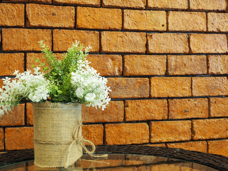 Decorated artificial flowers in flowerpot on glass table with re. D brick wall background royalty free stock photo