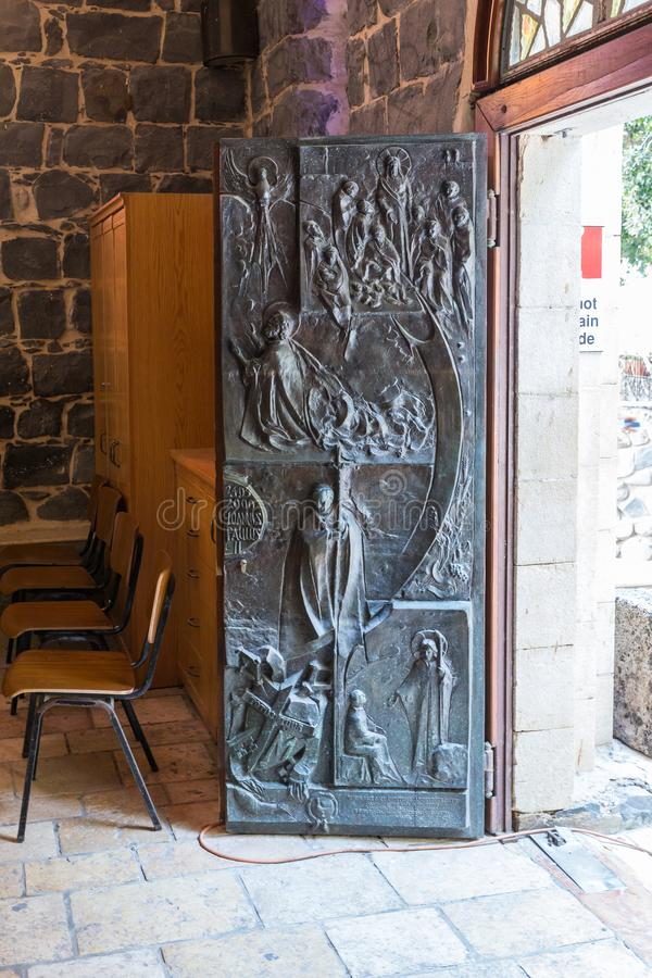 Decorated with bas-reliefs, the front door to the Church of the Primacy of Saint Peter located on the shores of the Sea of Galilee. Tiberias, Israel, September stock photos
