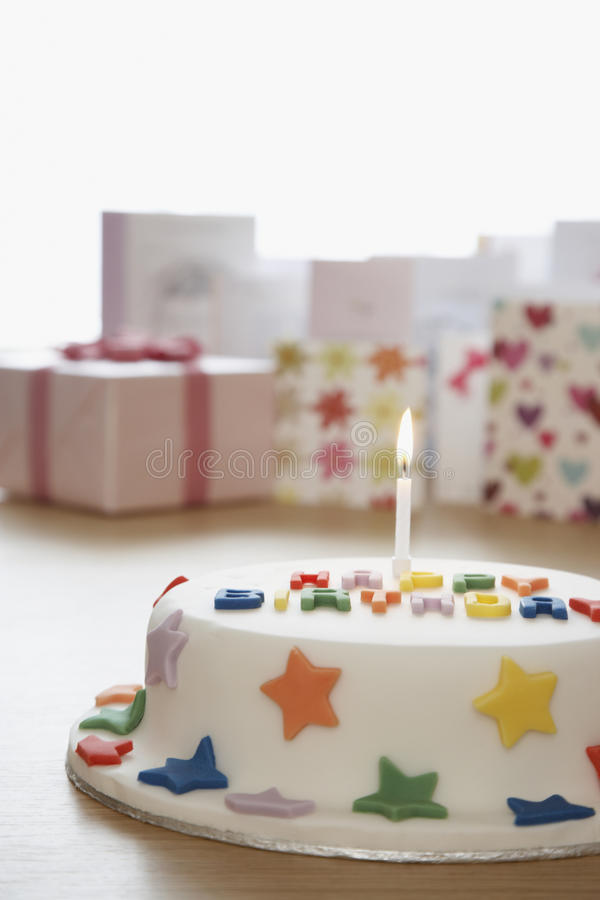 Decorated birthday cake with candle in front of cards in studio royalty free stock photo