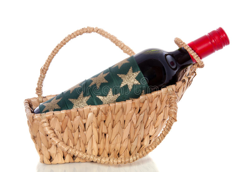 A decorated bottle of red wine. In a wicker basket isolated over white stock photography