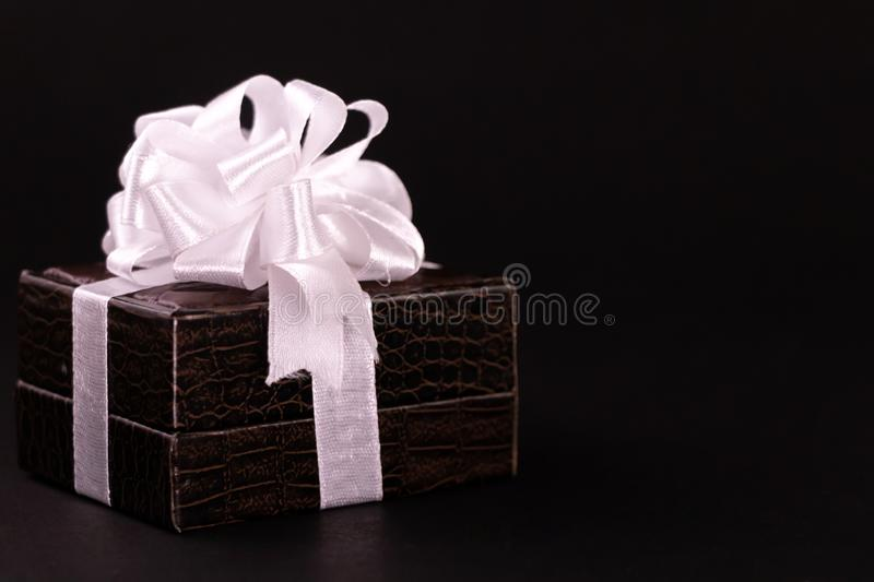 Decorated Brown gift box isolated on a dark background stock images