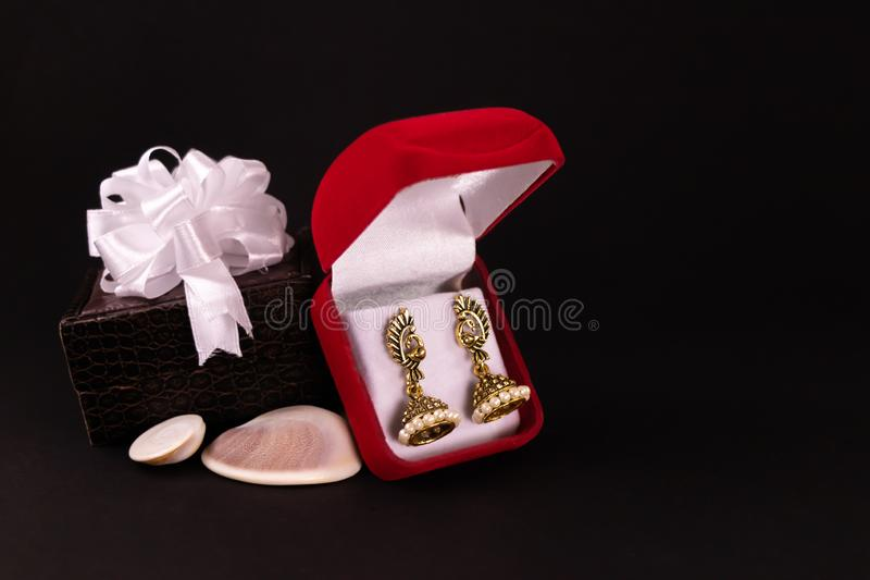 Decorated brown lether box and beautiful gold plated earrings in red gift box with seashells on black background. Anniversary gift royalty free stock photography