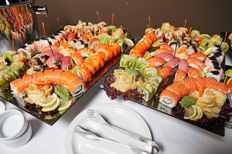 Decorated catering banquet table with different sushi rolls royalty free stock photography