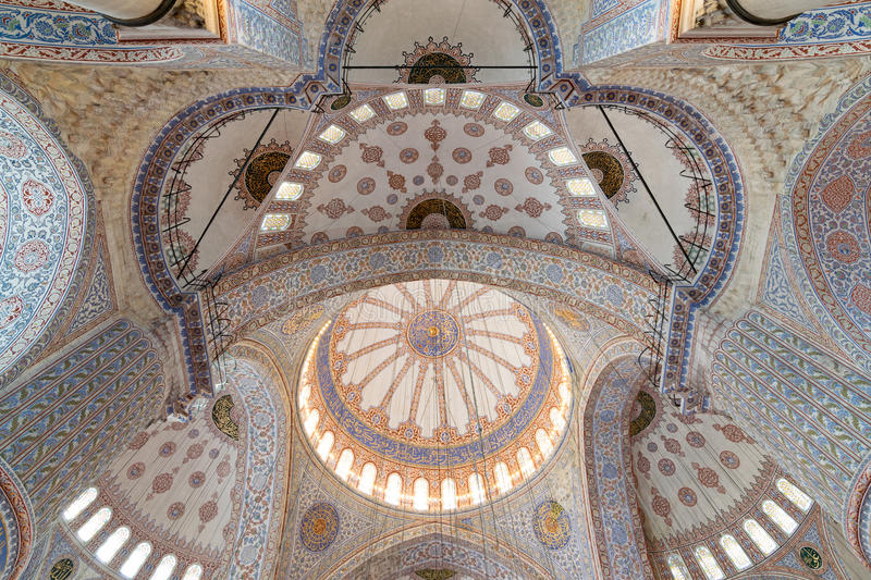 Decorated ceiling of the blue mosque with huge pillars, domes, arches and stained glass windows, Istanbul, Turkey royalty free stock photos