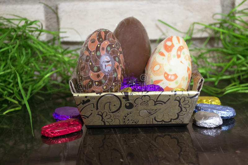 Decorated chocolate egg in basket and chocolates stock images