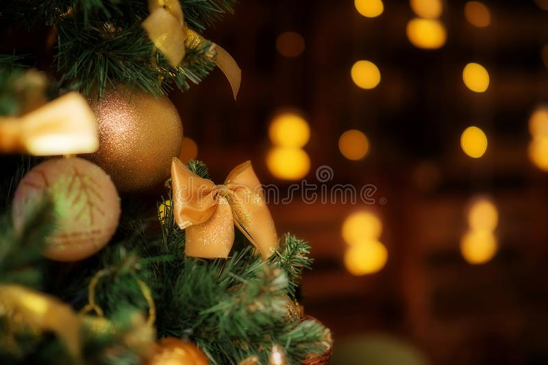 Christmas tree closeup with decorations: golden bow and balls. Blurred lights in the background. Room for copy text stock images