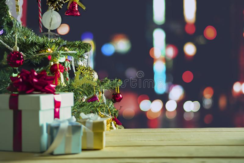 Decorated Christmas tree with blurred sparkling, bell and gift box set above abstract bokeh glitter background royalty free stock images