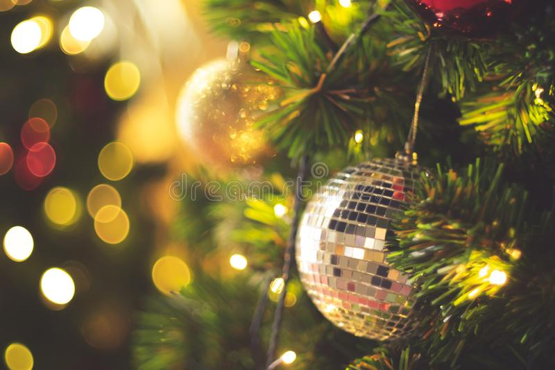 Decorated Christmas tree on blurred varicolored new year`s background  . Christmas Ornament On Wooden Background With Snowflakes, royalty free stock image