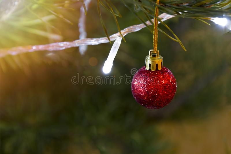 Decorated Christmas tree closeup. Red ball and illuminated garland with flashlights. Blurred New Year background royalty free stock photography