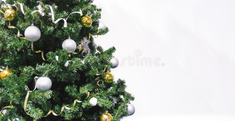 decorated Christmas tree with gifts close up on white background. Christmas tree decorated with yellow and white balls and tinsel. stock image