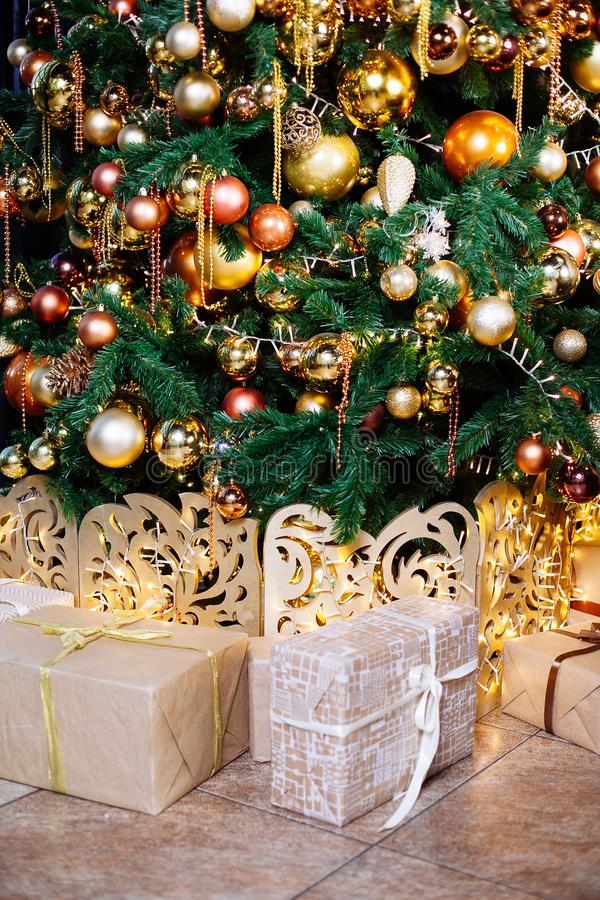 Decorated Christmas tree in gold and yellow colors. Merry Christmas and Happy New Year. Decorated Christmas tree in gold and yellow colors. Presents under the stock photo
