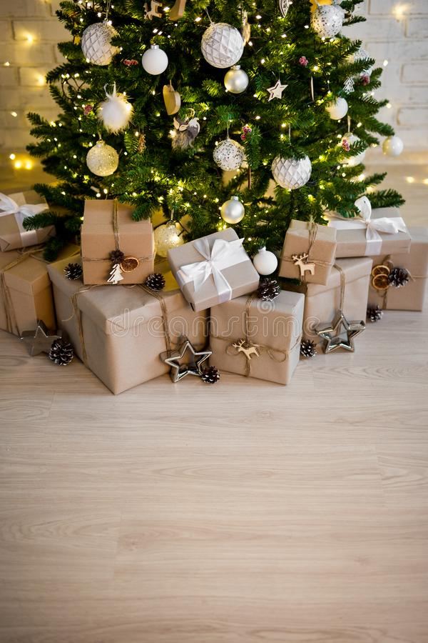 Decorated christmas tree and heap of gift boxes - copy space over wooden floor background royalty free stock images