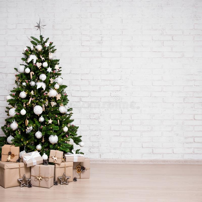 Free Decorated Christmas Tree, Heap Of Gift Boxes Over White Brick Wall With Copy Space Stock Photo - 163716580