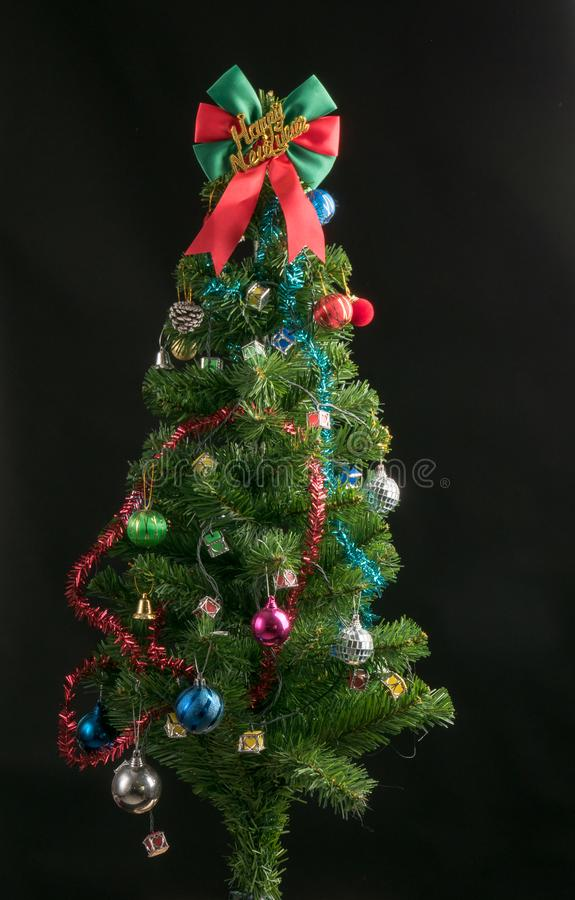 Decorated Christmas tree isolated on black background studio shot for family, giving, season, Christmas, holiday, new year, travel. Christian and gathering stock images