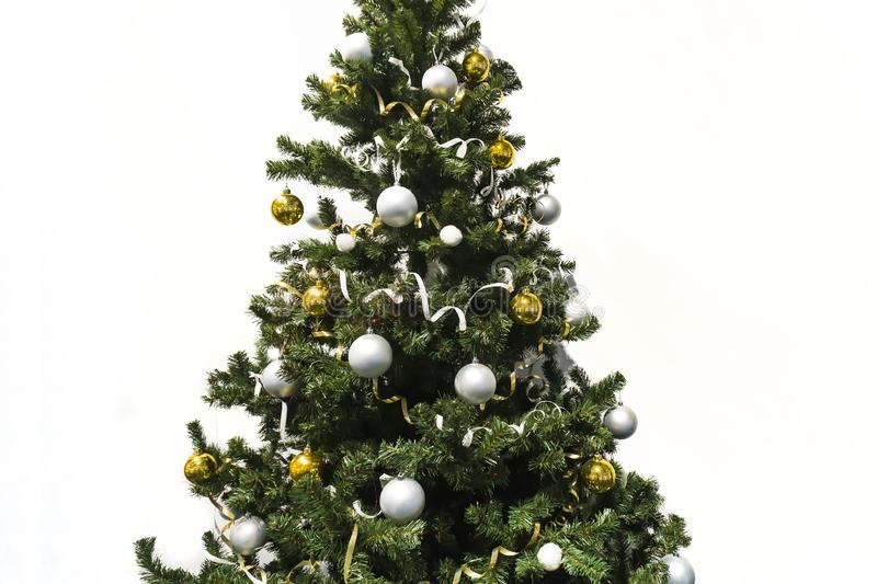 decorated Christmas tree isolated on white background. Christmas tree decorated with yellow and white balls and tinsel stock images