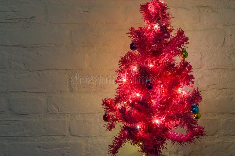 Decorated christmas tree with lighted lights isolated on a white brick wall background. A decorated christmas tree with lighted lights isolated on a white brick stock image
