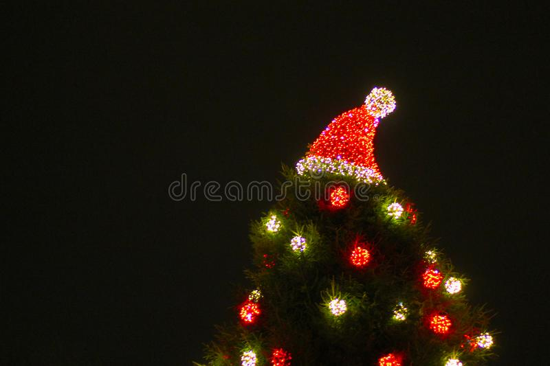 Decorated Christmas tree outdoor with lights and Santa hat royalty free stock image
