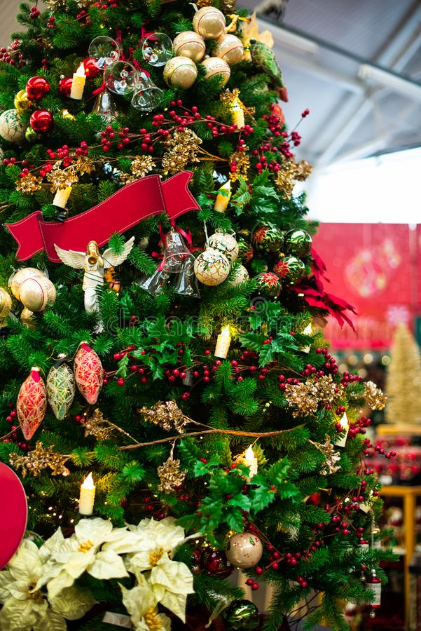 Decorated Christmas tree with red and golden decor, lights on blurred market background. Vertical card. Soft selective focus, copy royalty free stock images