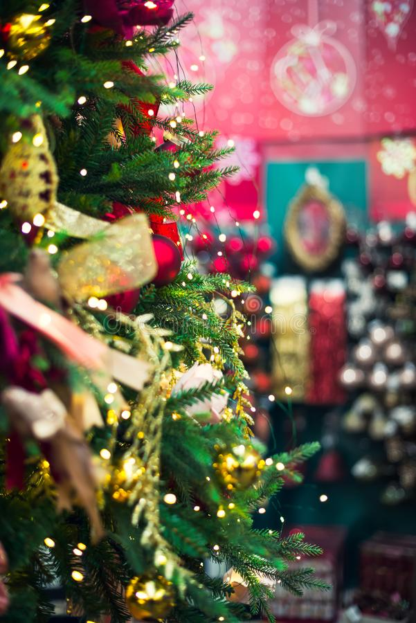 Decorated Christmas tree with red and golden decor, lights on blurred market background. Vertical card. Soft selective focus, copy stock photos