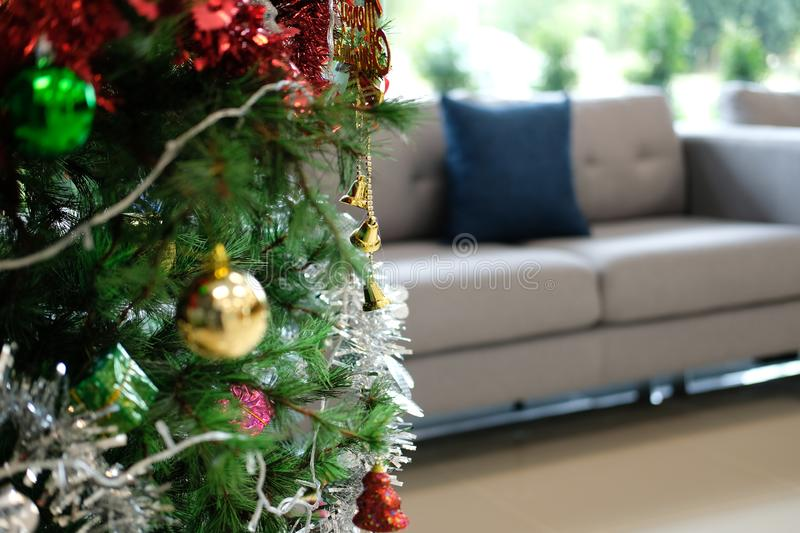 Decorated christmas tree & sofa couch in living room. xmas holiday celebration in december. Decorated christmas tree & gray sofa couch in living room. xmas royalty free stock photography