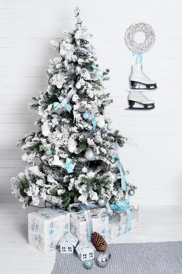 Decorated christmas tree on white background with skates and wreath hanging on the wall. New year decoration, winter stock image