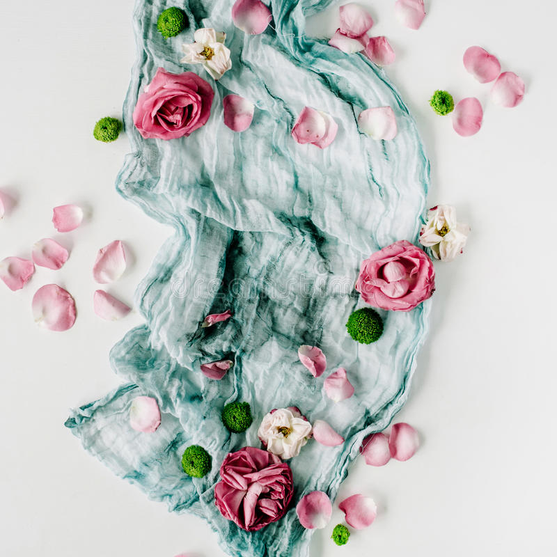 Decorated composition with dry red roses, pink petals and blue textile on white background stock image