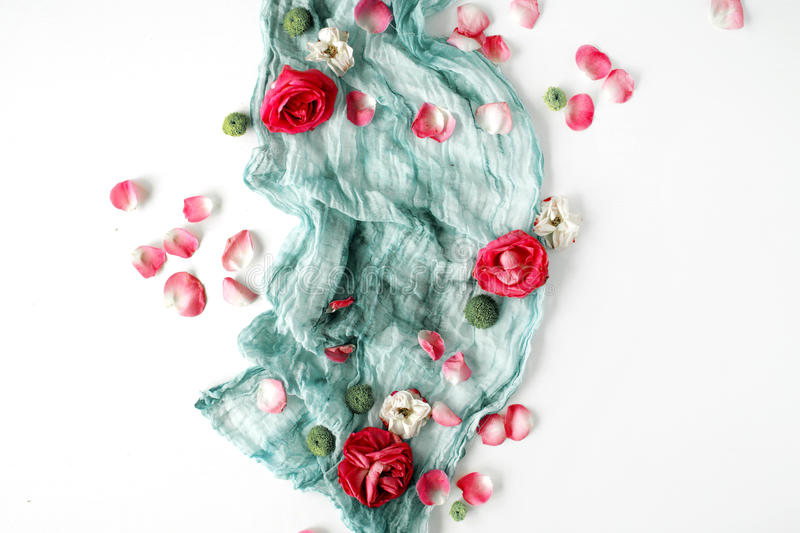 Decorated composition with red roses, pink petals and blue textile on white background stock images