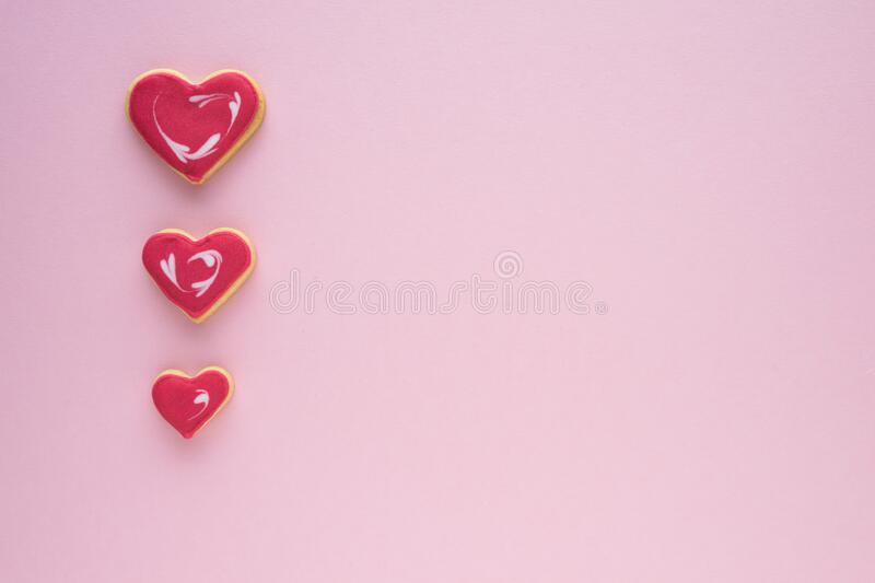 Decorated cookies of various sizes in the shape of a heart, on a pink background. Copy space. Valentine`s Day concept stock image