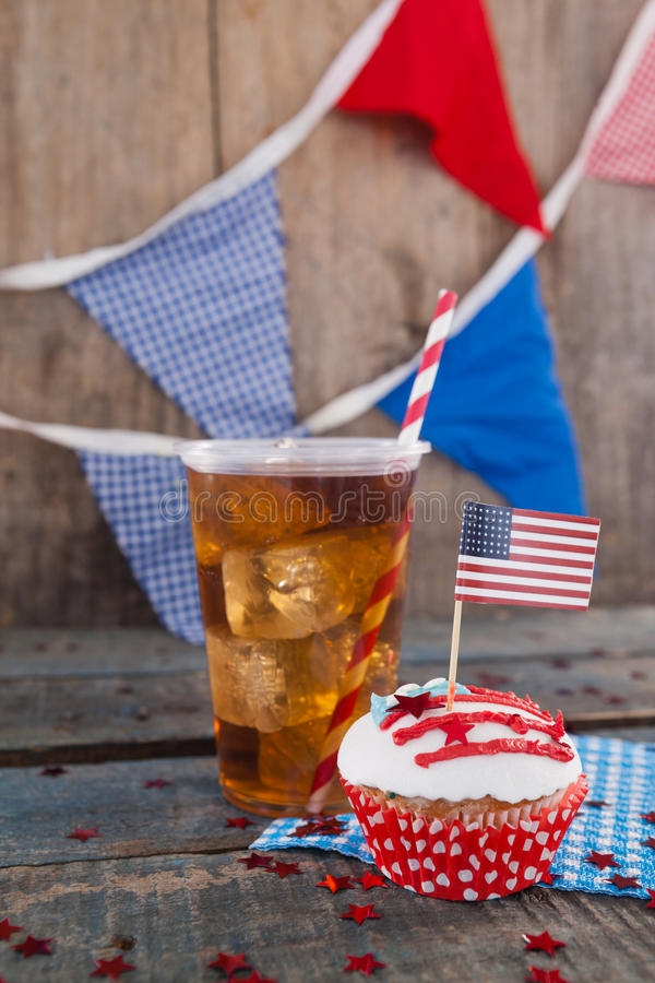 Decorated cupcake and cold drink with 4th july theme. On wooden table stock image